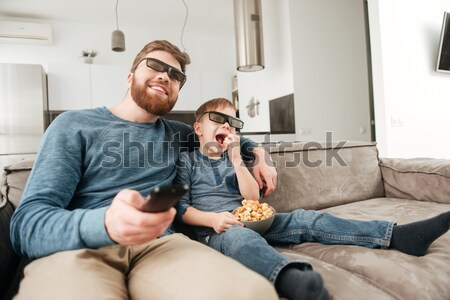 Stock fotó: Little boy watching TV with 3d glasses and holding popcorn